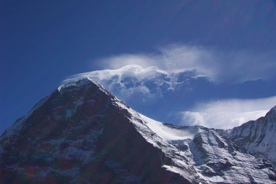 A banner cloud, with the appearance of strong turbulence, forming at the peak of the Eiger mountain in Switzerland.