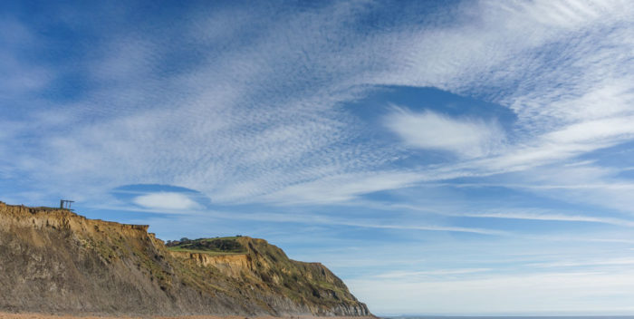 A pair of fallstreak holes over Seatown beach, Dorset, UK.