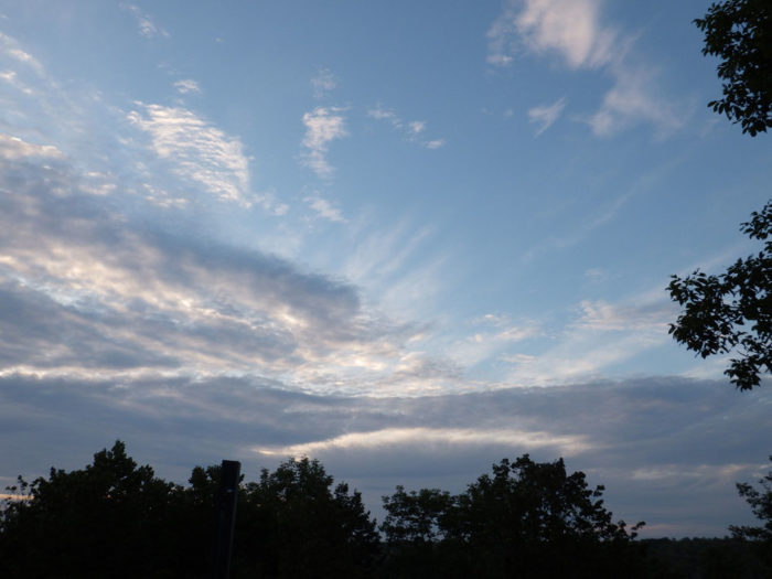 A sunset with a fallstreak hole and crepuscular rays over North Otter Lake, South Frontenac, Ontario, Canada.