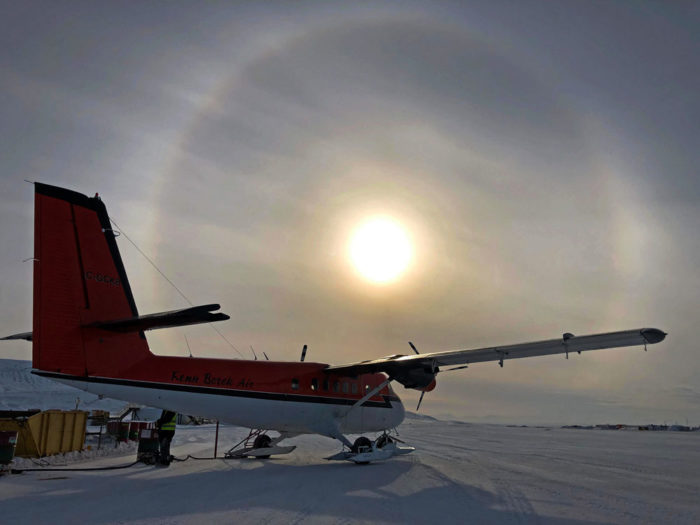 A halo encircles the sun over a Twin Otter aircraft at the Eureka, Canada airfield on Ellesmere Island.